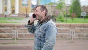 Πορτρέτο του όμορφου νεαρού άνδρα με τη γενειάδα και στην ομιλία στο κινητό τηλέφωνο υπαίθρια κλείστε επάνω απόθεμα βίντεο