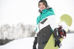 Πορτρέτο του όμορφου νεαρού άνδρα με το σνόουμπορντ στο χιόνι Στοκ Φωτογραφίες