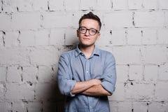 Πορτρέτο του όμορφου νεαρού άνδρα στα ενδύματα και eyeglasses τζιν που εξετάζει τη κάμερα που χαμογελά, που στέκεται ενάντια στο  Στοκ φωτογραφία με δικαίωμα ελεύθερης χρήσης