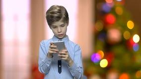 Πορτρέτο του όμορφου παιδιού που χρησιμοποιεί το smartphone φιλμ μικρού μήκους