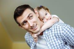 Πορτρέτο του όμορφου πατέρα και της χαριτωμένης κόρης του που αγκαλιάζουν και που χαμογελούν Στοκ φωτογραφία με δικαίωμα ελεύθερης χρήσης