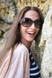 Πορτρέτο του όμορφου προτύπου που κλίνει ενάντια στο χαμόγελο βράχων στοκ εικόνα με δικαίωμα ελεύθερης χρήσης