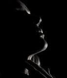 Πορτρέτο του όμορφου σχεδιαγράμματος κοριτσιών αισθησιασμού σκεπτικού με τις ιδιαίτερες προσοχές σε ένα σκοτάδι, σε ένα μαύρο υπό Στοκ Φωτογραφία