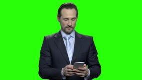 Πορτρέτο του όμορφου ώριμου καυκάσιου ατόμου που χρησιμοποιεί το smartphone του φιλμ μικρού μήκους