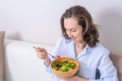 Πορτρέτο του brunette χαμόγελου που τρώει το φρέσκο λαχανικό, χορτοφάγος σαλάτα στοκ εικόνα