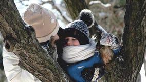 Πορτρέτο του mom και λίγου γιου χιονωδών το χειμώνα κοντά σε ένα δέντρο φιλμ μικρού μήκους