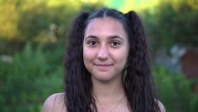 Πορτρέτο Το όμορφο κορίτσι εξετάζει τη κάμερα και χαμογελά φιλμ μικρού μήκους