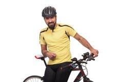 Πορτρέτο το bicyclist με το κράνος και το κίτρινο πουκάμισο, που θέτει με ένα ποδήλατο, που απομονώνεται στο λευκό Στοκ Φωτογραφία