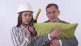 Πορτρέτο τρελλού στενού επάνω ζευγών Ο άνδρας κρατά το μαξιλάρι, γυναίκα στο μπουκάλι σαμπάνιας κρανών που απομονώνεται στο άσπρο απόθεμα βίντεο