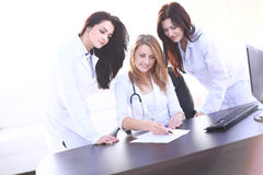 Πορτρέτο τριών βέβαιων θηλυκών γιατρών που στέκονται με τα όπλα που διασχίζονται Στοκ Εικόνες