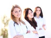 Πορτρέτο τριών βέβαιων θηλυκών γιατρών που στέκονται με τα όπλα που διασχίζονται Στοκ εικόνες με δικαίωμα ελεύθερης χρήσης