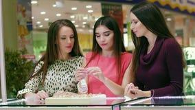 Πορτρέτο τριών θηλυκών φίλων που κοιτάζουν και που προσπαθούν στα δαχτυλίδια στη λεωφόρο αγορών φιλμ μικρού μήκους
