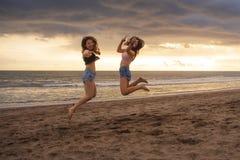 Πορτρέτο τρόπου ζωής δύο ευτυχών και ελκυστικών νέων ασιατικών κορεατικών φίλων γυναικών που πηδούν στην παραλία ηλιοβασιλέματος  στοκ εικόνα