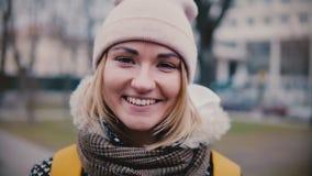 Πορτρέτο τρόπου ζωής κινηματογραφήσεων σε πρώτο πλάνο του νέου όμορφου καυκάσιου κοριτσιού στο χαμόγελο χειμερινών καπέλων ευτυχέ φιλμ μικρού μήκους
