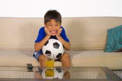 Πορτρέτο τρόπου ζωής στο σπίτι σφαίρα ποδοσφαίρου εκμετάλλευσης νεολαιών χρονών των αγοριών 7 ή 8 που προσέχει το συγκινημένο και στοκ φωτογραφίες