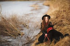 Πορτρέτο τρόπου ζωής της νέας γυναίκας στο μαύρο καπέλο με το σκυλί της, που στηρίζεται από τη λίμνη σε μια συμπαθητική και θερμή στοκ φωτογραφία με δικαίωμα ελεύθερης χρήσης
