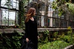 Πορτρέτο τρόπου ζωής του κοριτσιού που φορά την κενά μαύρα μπλούζα, τα τζιν και την τοποθέτηση παλτών ενάντια στο κτήριο που καλύ Στοκ Φωτογραφία