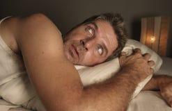 Πορτρέτο τρόπου ζωής του νέου ελκυστικού φοβησμένου και παρανοϊκού ατόμου που βρίσκεται στο κρεβάτι που έχει τα κακούς όνειρα και στοκ εικόνα
