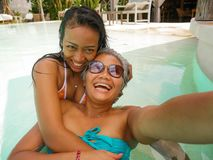 Πορτρέτο τρόπου ζωής υπαίθρια των ασιατικών φίλων που απολαμβάνουν τις καλοκαιρινές διακοπές στην τροπική πισίνα παραθαλάσσιων θε στοκ φωτογραφία