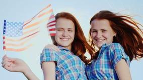 Πορτρέτο των δίδυμων κοριτσιών με τη αμερικανική σημαία Εξετάζοντας τη κάμερα ενάντια στο μπλε ουρανό, χαμόγελο ανεξαρτησία ημέρα απόθεμα βίντεο