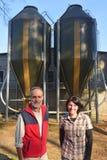 Πορτρέτο των αγροτών ζευγών έξω από ένα grange με το σιτάρι storege στοκ εικόνες