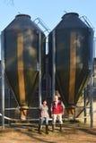 Πορτρέτο των αγροτών ζευγών έξω από ένα grange με το σιτάρι storege στοκ φωτογραφία με δικαίωμα ελεύθερης χρήσης