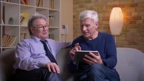 Πορτρέτο των ανώτερων αρσενικών φίλων που κάθονται μαζί στις swiping φωτογραφίες καναπέδων στην ταμπλέτα και που γελούν ευτυχώς απόθεμα βίντεο
