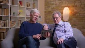 Πορτρέτο των ανώτερων αρσενικών φίλων που κάθονται μαζί στον καναπέ που μιλά στο videochat στην ταμπλέτα που είναι ευτυχή απόθεμα βίντεο