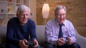 Πορτρέτο των ανώτερων αρσενικών φίλων που παίζουν videogame που χρησιμοποιεί την κονσόλα πηδαλίων και παιχνιδιών που είναι ευτυχή φιλμ μικρού μήκους