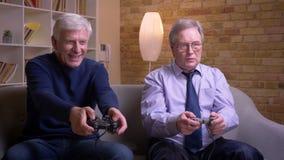 Πορτρέτο των ανώτερων αρσενικών φίλων που παίζουν videogame που χρησιμοποιεί την κονσόλα πηδαλίων και παιχνιδιών που χάνει και πο απόθεμα βίντεο