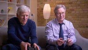 Πορτρέτο των ανώτερων αρσενικών φίλων που παίζουν videogame που χρησιμοποιεί την κονσόλα πηδαλίων και παιχνιδιών που αισθάνεται τ απόθεμα βίντεο