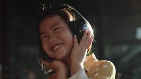 Πορτρέτο των ασιατικών παιδιών που ακούνε τη μουσική στην επικεφαλής συγκίνηση ευτυχίας τηλεφωνικού οδοντωτή χαμόγελου απόθεμα βίντεο