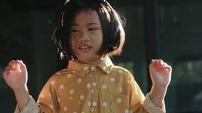 Πορτρέτο των ασιατικών παιδιών που ακούνε τη μουσική στο επικεφαλής τηλεφωνικό οδοντωτό sm φιλμ μικρού μήκους