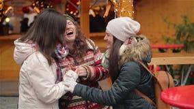 Πορτρέτο των γελώντας φίλων που έχουν τη διασκέδαση στην αγορά Χριστουγέννων Οι ευτυχείς φίλοι ξοδεύουν το χρόνο μαζί κατά τη διά φιλμ μικρού μήκους