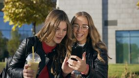 Πορτρέτο των δύο μοντέρνων καλύτερων φίλων γυναικών σπουδαστών που πίνουν το φρέσκο χυμό, που διαβάζει κάτι στο smartphone και φιλμ μικρού μήκους