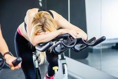 Πορτρέτο των εξαντλημένων περιστρεφόμενων πενταλιών γυναικών στο ποδήλατο άσκησης Στοκ Εικόνες