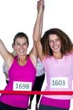 Πορτρέτο των ευτυχών αθλητών νικητών που διασχίζουν τη γραμμή τερματισμού με τα όπλα που αυξάνεται Στοκ Φωτογραφία
