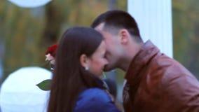 Πορτρέτο των ευτυχών εραστών ερωτευμένων στο πάρκο το ευτυχές και αμήχανο κορίτσι αγκαλιάζει έναν τύπο κατά μια ρομαντική ημερομη φιλμ μικρού μήκους