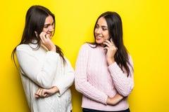 Πορτρέτο των ευτυχών κοριτσιών που μιλούν στα κινητά τηλέφωνα που απομονώνονται πέρα από το κίτρινο υπόβαθρο Στοκ Εικόνες