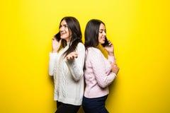 Πορτρέτο των ευτυχών κοριτσιών που μιλούν στα κινητά τηλέφωνα που απομονώνονται πέρα από το κίτρινο υπόβαθρο Στοκ Φωτογραφίες