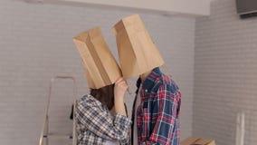 Πορτρέτο των ευτυχών νέων που βάζουν στις τσάντες εγγράφου κεφαλιών τους, εγκαίνια σπιτιού απόθεμα βίντεο