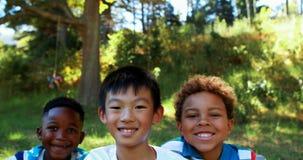 Πορτρέτο των ευτυχών παιδιών που κάθονται στο πάρκο απόθεμα βίντεο