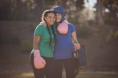 Πορτρέτο των ευτυχών φίλων που αγκαλιάζει το ένα το άλλο κατά τη διάρκεια της σειράς μαθημάτων εμποδίων Στοκ Εικόνες