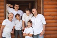 Πορτρέτο των ευτυχών όμορφων ατόμων στο υπόβαθρο του ξύλινου σπιτιού στοκ εικόνες