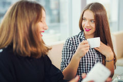 Πορτρέτο των κοριτσιών εφήβων που κάθονται στον πίνακα στον καφέ, που έχει τη διασκέδαση από κοινού Στοκ Εικόνες