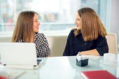 Πορτρέτο των κοριτσιών εφήβων που κάθονται στον πίνακα στον καφέ Στοκ Εικόνες