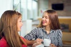 Πορτρέτο των κοριτσιών εφήβων που κάθονται στον πίνακα στον καφέ Στοκ Φωτογραφία