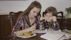 Πορτρέτο των μαθημάτων εκμάθησης παλαιότερων αδελφών και μικρότερων αδερφών Ένα κορίτσι κάνει την εργασία με ένα μικρό αγόρι απόθεμα βίντεο