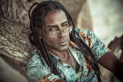 Πορτρέτο των μαύρων με τα dreadlocks, τα γυαλιά και ένα φανταχτερό πουκάμισο Στοκ Φωτογραφίες