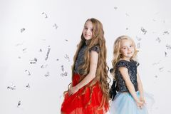 Πορτρέτο των μικρών κοριτσιών με το σγουρό hairstyle που στέκεται στο κόμμα διακοπών στο φόρεμα με τα τσέκια Εορτασμός έννοιας Στοκ εικόνες με δικαίωμα ελεύθερης χρήσης